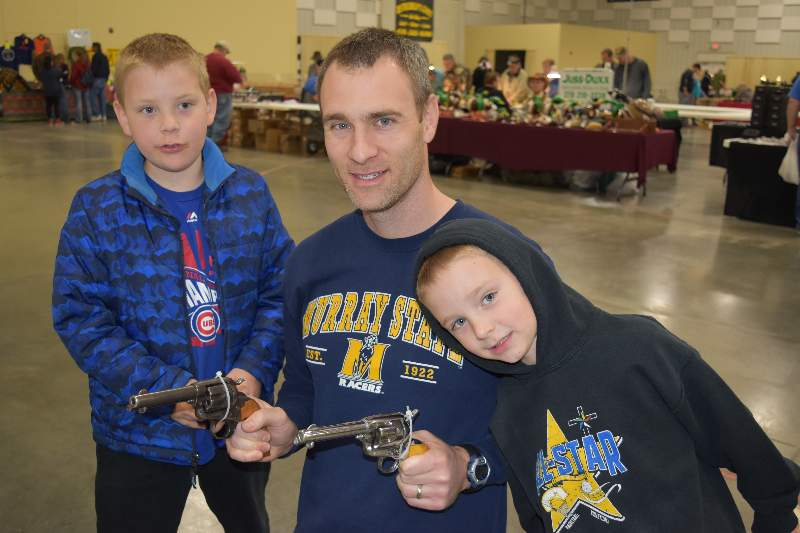 Daniel Wenzel, center, along with his sons Jacob (left) and Ethan, display a pair of revolvers owned his father, Ken Wenzel.