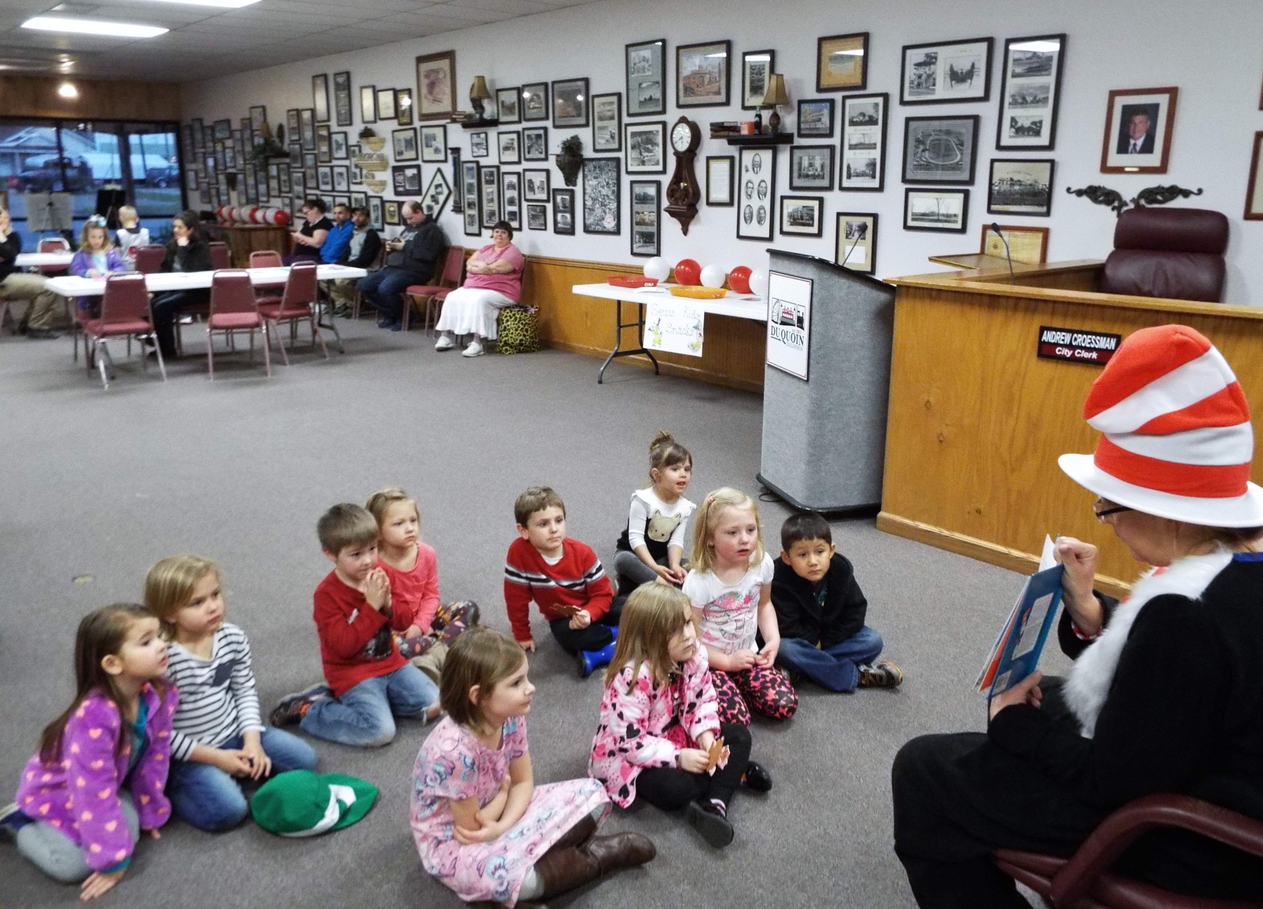 The Cat in the Hat -- also known as Sherry DeAngelo, assistant coordinator for the John A. Logan College Family Literacy Program -- reads 'The Cat in the Hat Comes Back' to the Du Quoin children and parents who came to Dr. Seuss' birthday party Monday at city hall.