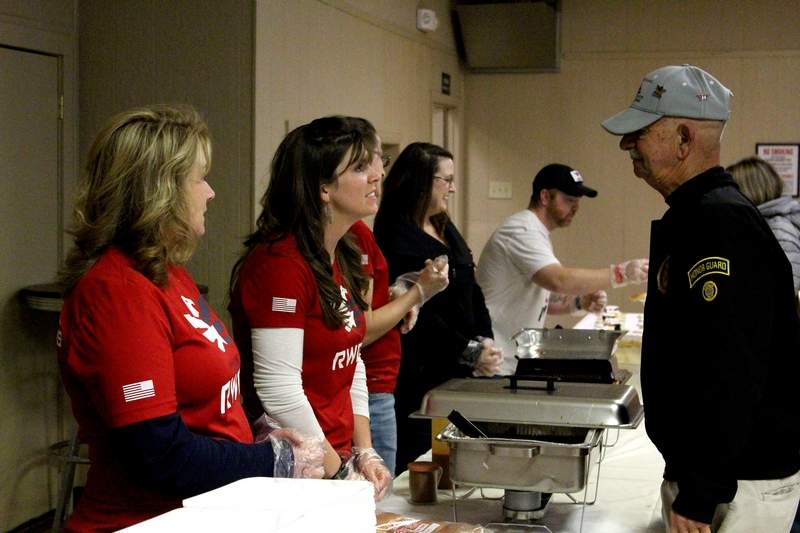 Kim Ecker (far left) of Makanda and Amanda Korando (left) of Marion speak with Dan Fike at the Marion VFW on Friday night. Korando and Ecker were helping to serve food, while volunteering with Team RWB, a civilian/veteran volunteer organization. Proceeds from Friday's dinner went to support the Veterans Honor Flight of Southern Illinois.