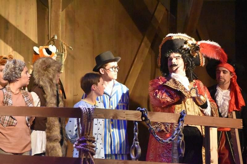 Captain Hook (Alex McRoy) prepares to send the Darling boys (Landon Gates and Luke Winkleman) to walk the plank.