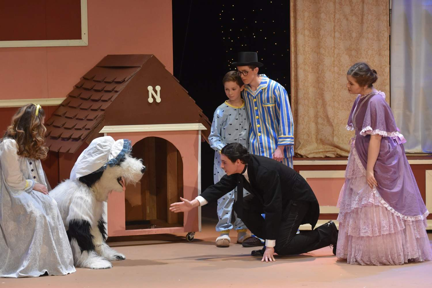 Mr. Darling (Kole Phelps) tries to catch the family's sheepdog Nana (Anthony Cortes).