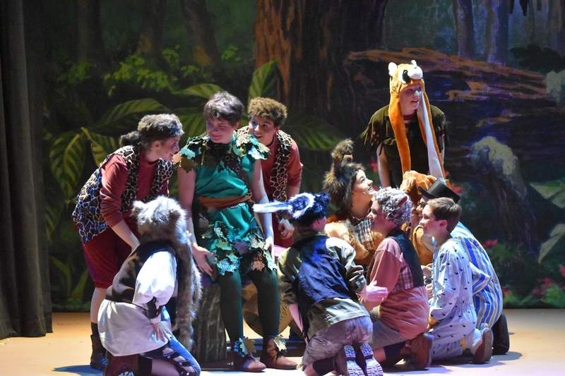 """The Lost Boys gather around Peter Pan to learn that he has brought Wendy to be their new """"mother."""""""