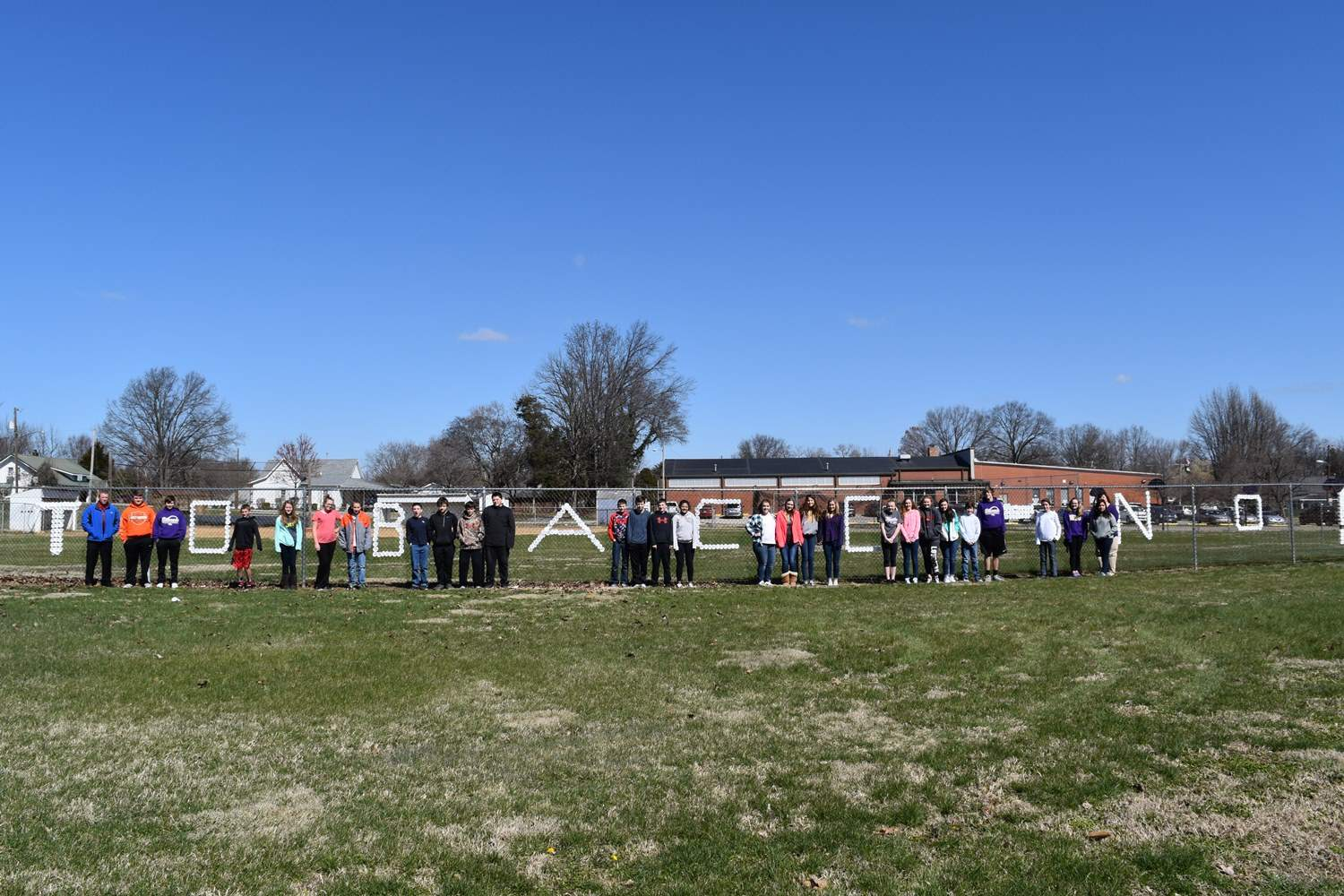 """Eldorado Middle School Junior Beta members observe the anti-tobacco message at the school's chain link fence. The message was placed by Eldorado High School students, under the guidance of the Egyptian Health Department as part of """"Kick Butts Day,"""" a national awareness campaign about the dangers of tobacco products."""