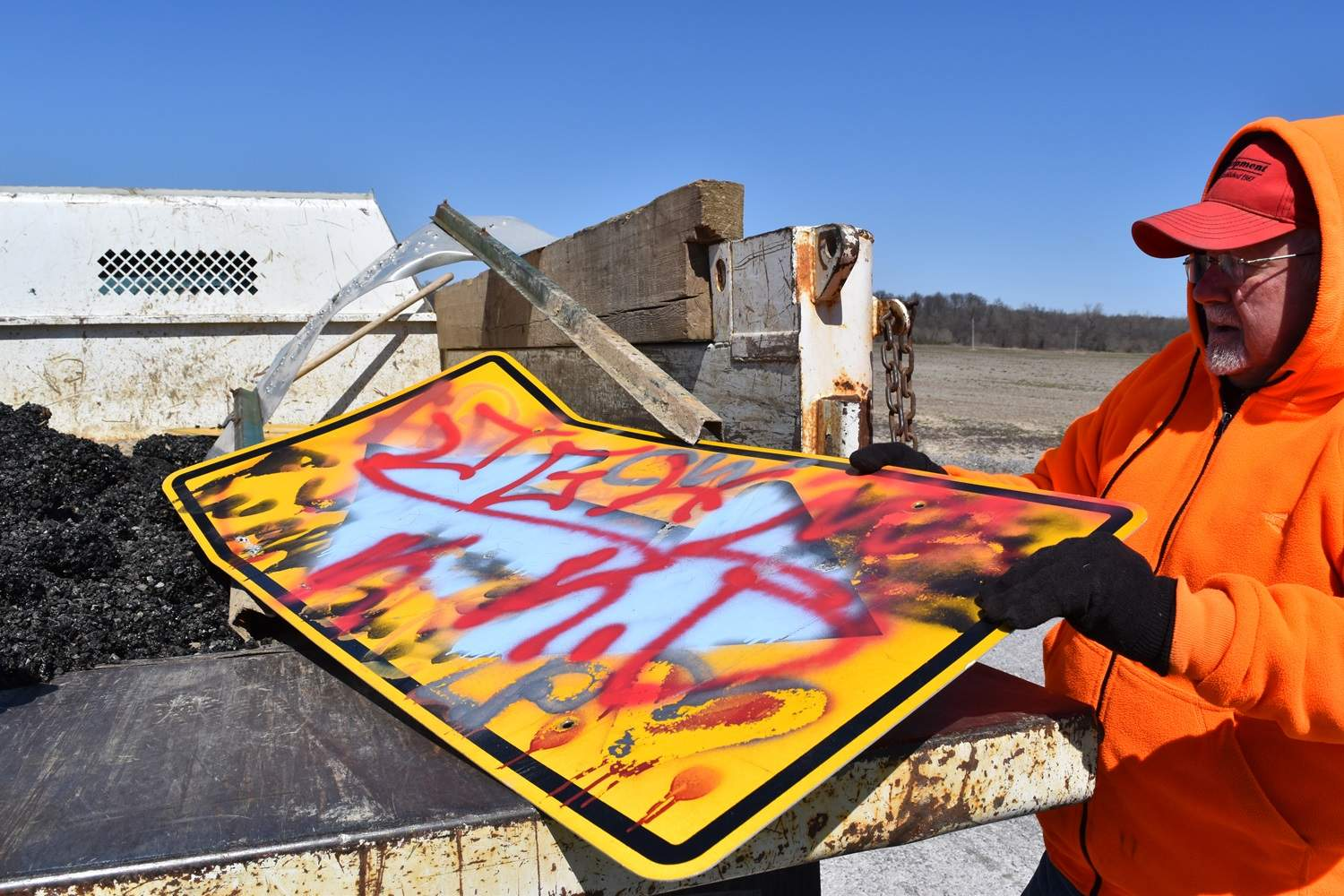 Harrisburg Township Road Commissioner Bob Holmes displays two recently vandalized signs from Mt. Moriah Road, north of Harrisburg. Holmes said sign vandalism is increasing, which costs townships significant money.