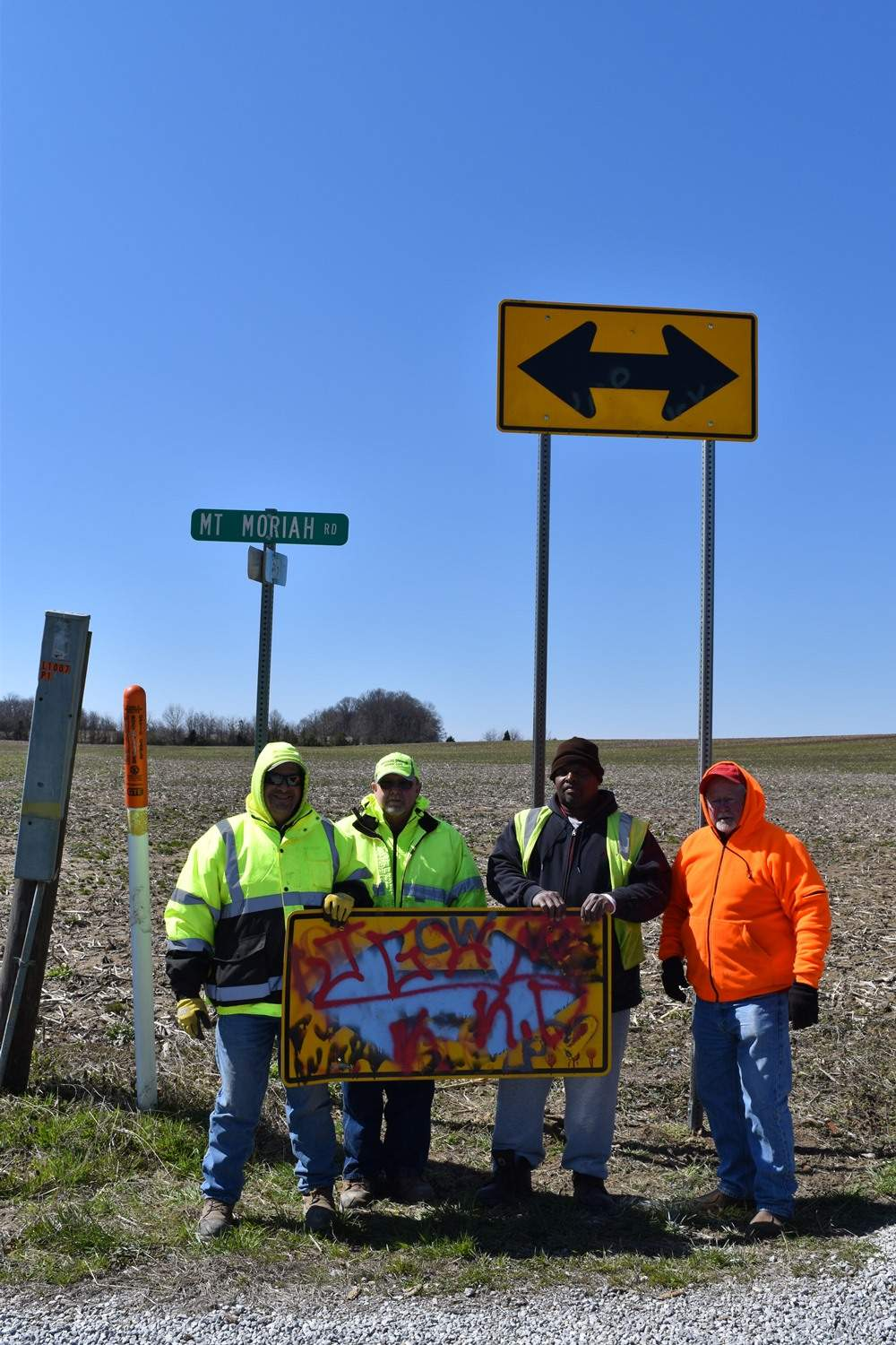 From left, Harrisburg Township workers Charlie Hyers and Rick Duffy, Earnfare worker Eric McWilliams and Road Commissioner Bob Holmes shows a sign vandalized within and hour or two of placement Tuesday afternoon, along with a new replacement sign that is elevated 10 feet to minimize damage from vandals.