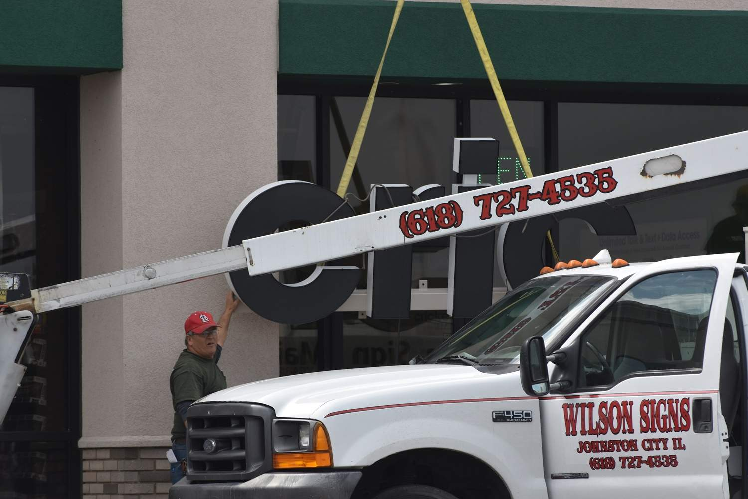Workers from Wilson Signs in Johnston City installed a sign at the new Cricket Wireless office at 716 Rollie Moore Drive.