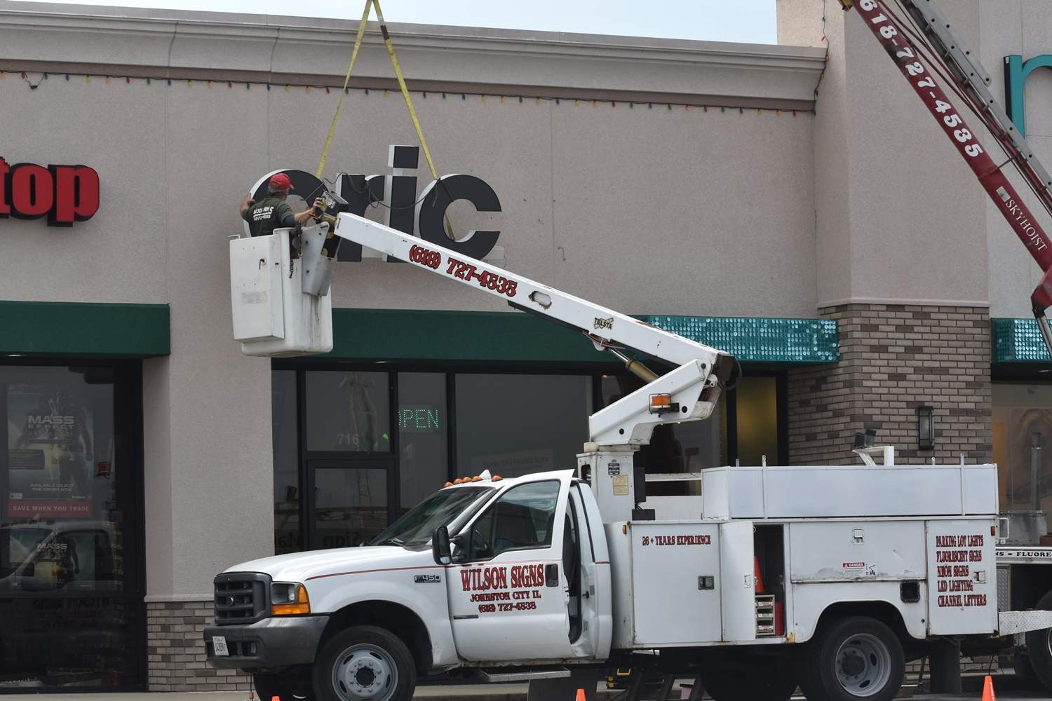 The new sign goes up.