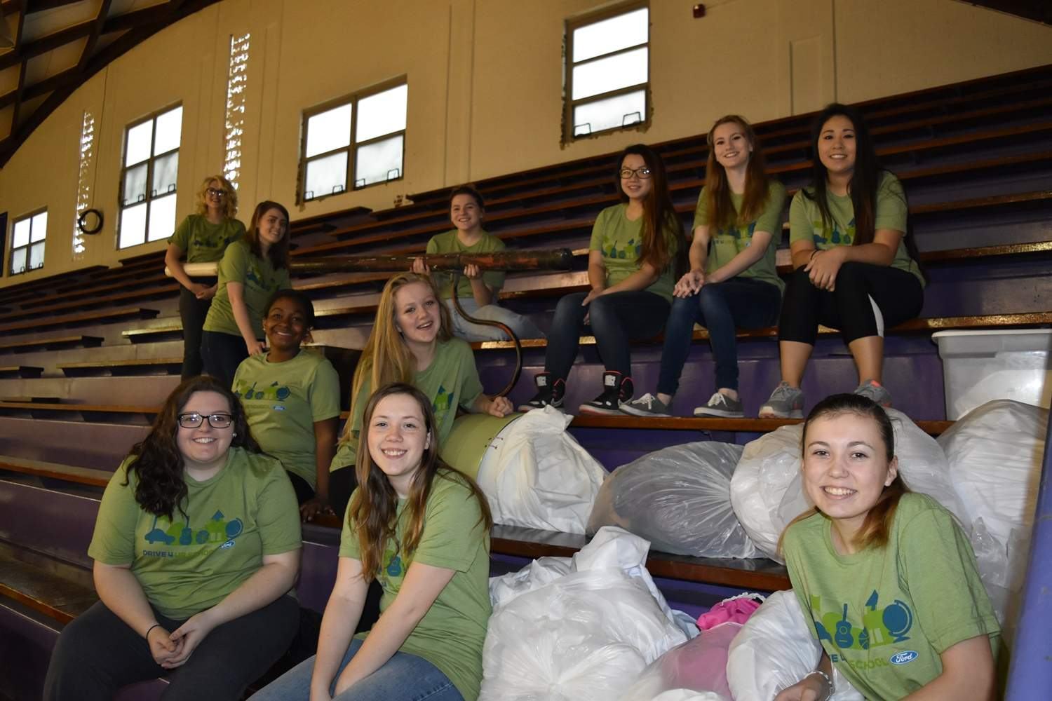 A group of band and color guard volunteer students pause for a break during organizing rummage sale items.