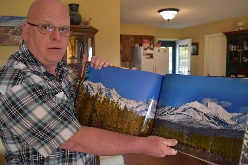 Randy Butler of Harrisburg displays a panorama of a mountain range in Montana from one of his two photo books.