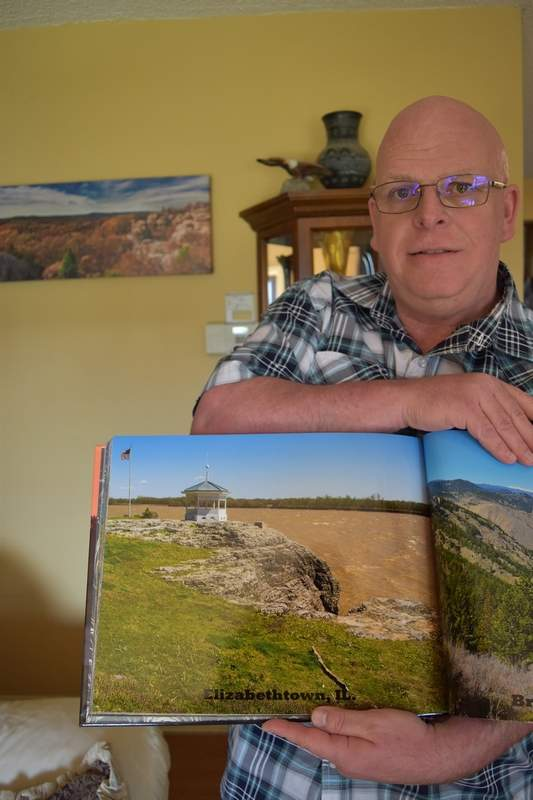 Randy Butler of Harrisburg displays a photo of the gazebo overlooking the river in Elizabethtown from one of his two photo books.