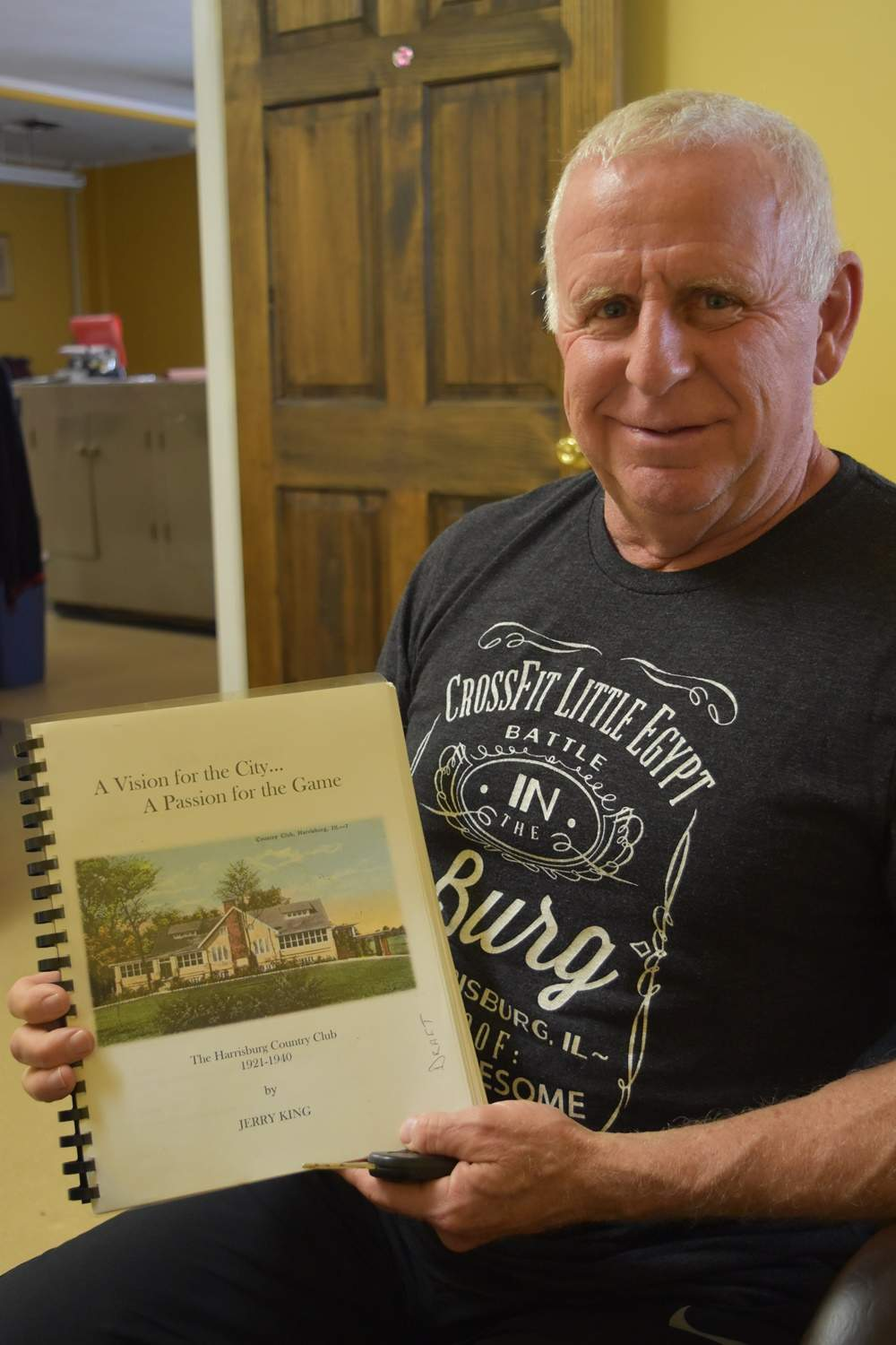 Shawnee Hills member Jerry King displays a copy of his history of the Harrisburg golf club.