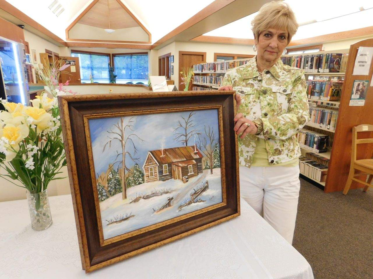 Artist Sandra Long displays her first winter scene, which will now have a home on the Wall of Art at the Benton Public Library.