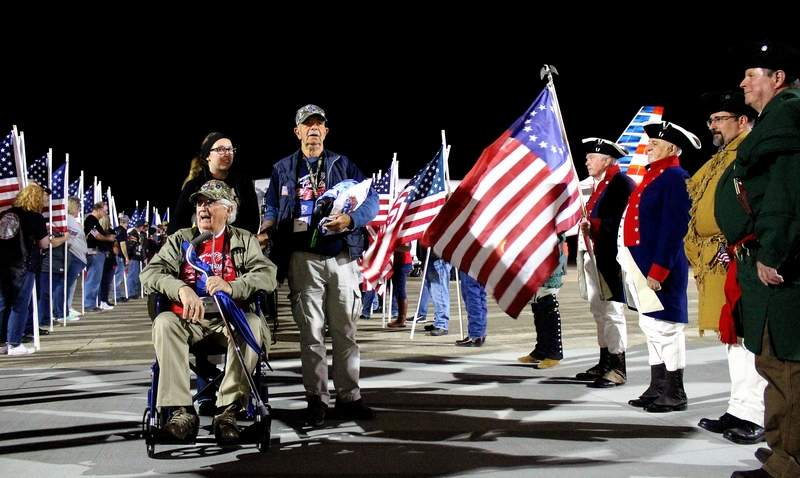 Don Cooper of Harrisburg (seated) was awed by the crowd that greeted him and his fellow Honor Flight veterans when they returned to the Veterans Airport of Southern Illinois on Tuesday night. The entire airport was packed, as well as most of the tarmac area, with family, friends, and community members wishing to thank the veterans for their service to the country.