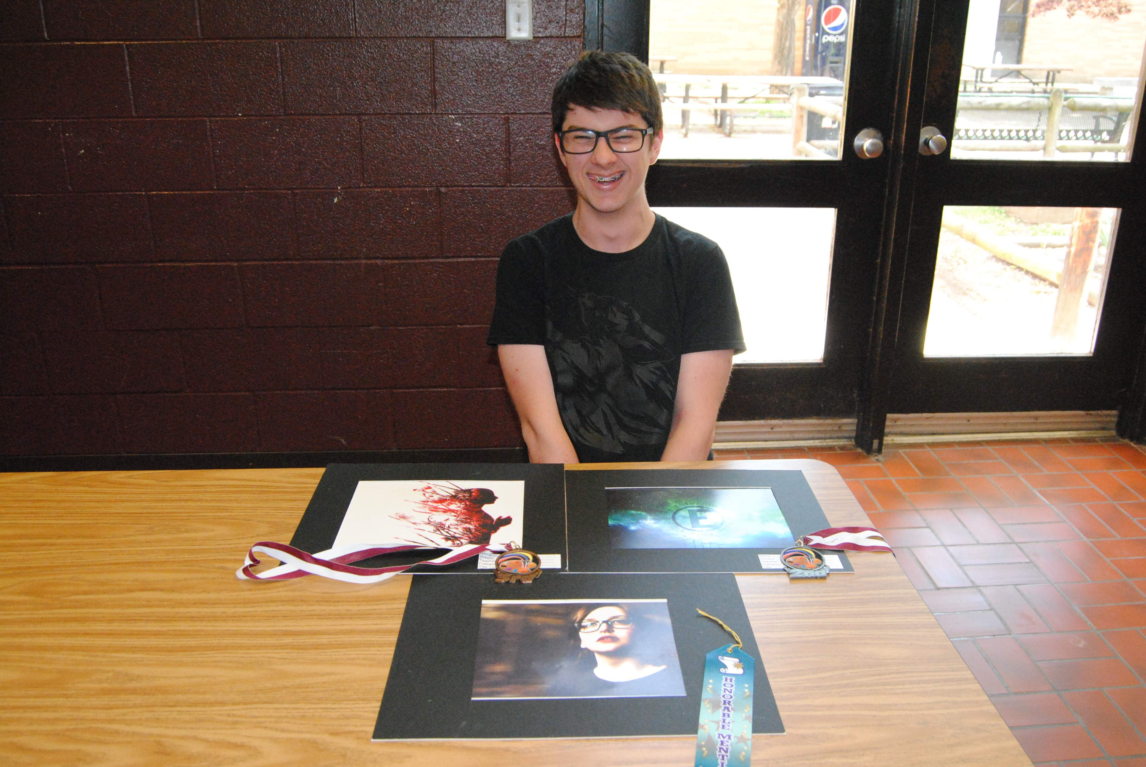 Noah Bishop is happy with his three wins from the Pope County High School art competition. Bishop took second and third places in computer graphics plus an honorable mention in photography.