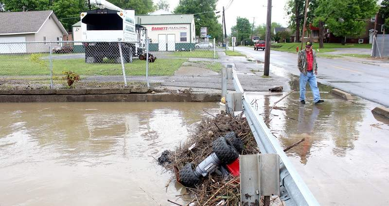 Charles Bell examines the debris brought up by the high waters at the East Main Street bridge over Mule Creek on Saturday. The high waters were blocked from flowing in the creek by the vast amount of debris - including a child's toy 4-wheeler, and as a result had begun overflowing onto the street.