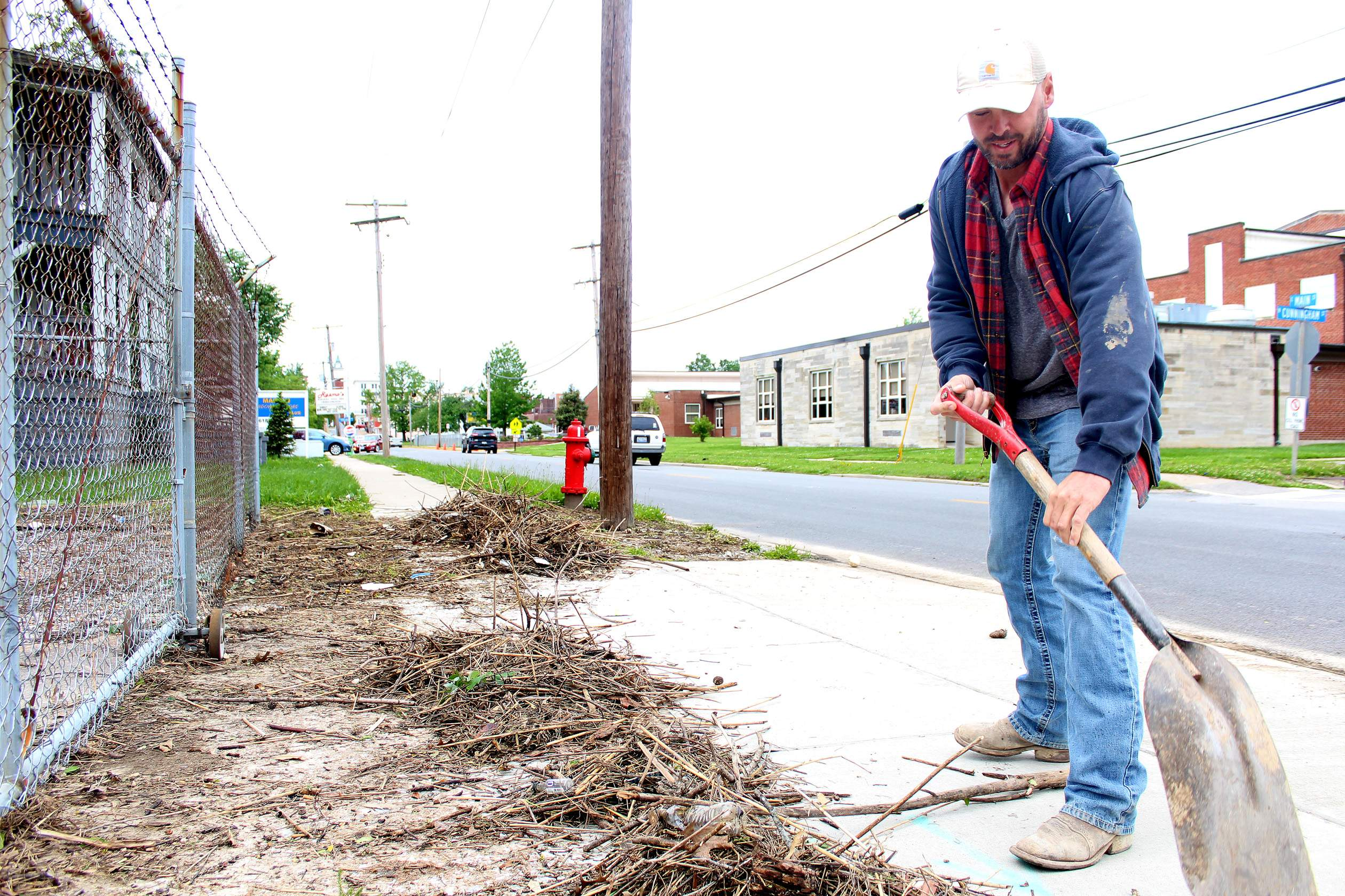 Marion Street Department worker Eddie Frey scoops up debris alongside East Main Street in downtown Marion on Monday. The weekend's storms had left sticks, branches, and other messes in the roads, along gutters, and caught in fences for Frey and city employees to clean up.