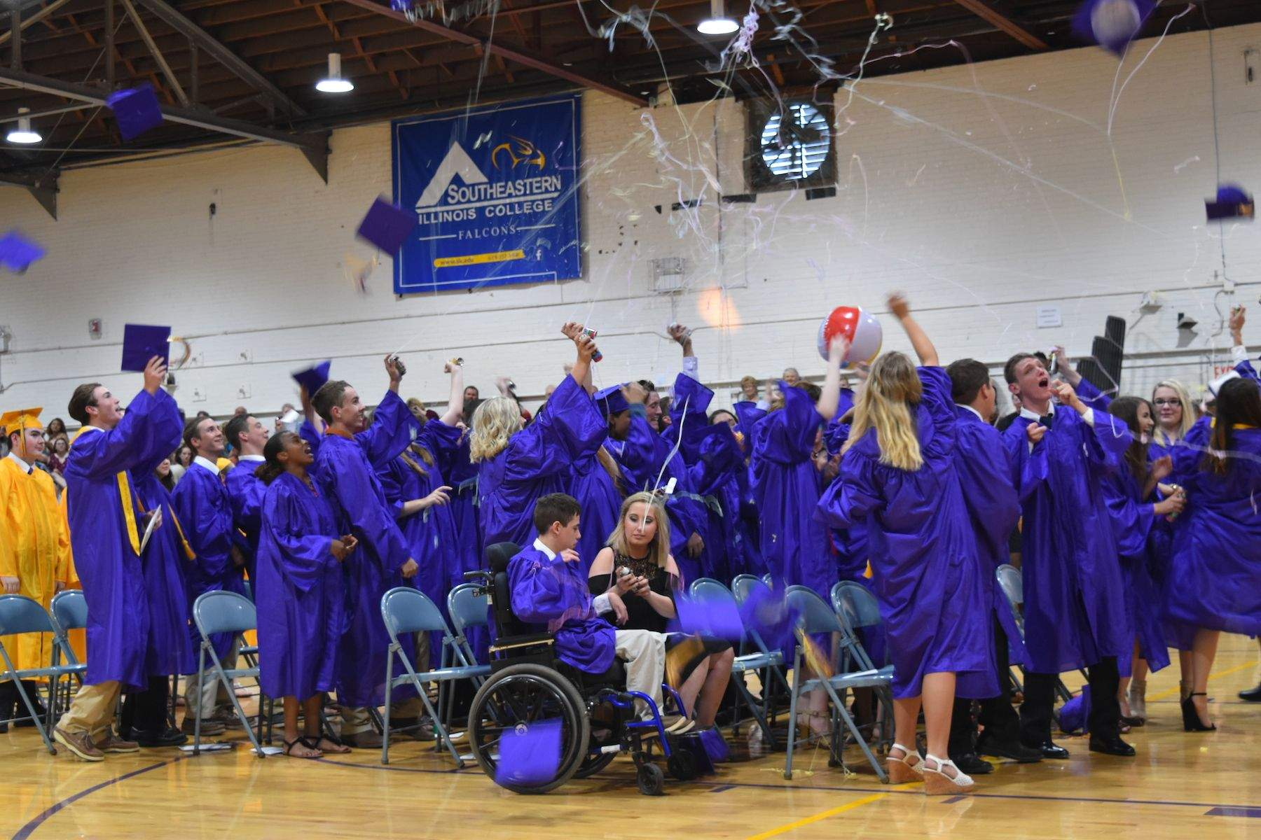 "Graduates celebrate by tossing their mortarboards and squirting ""silly string."""