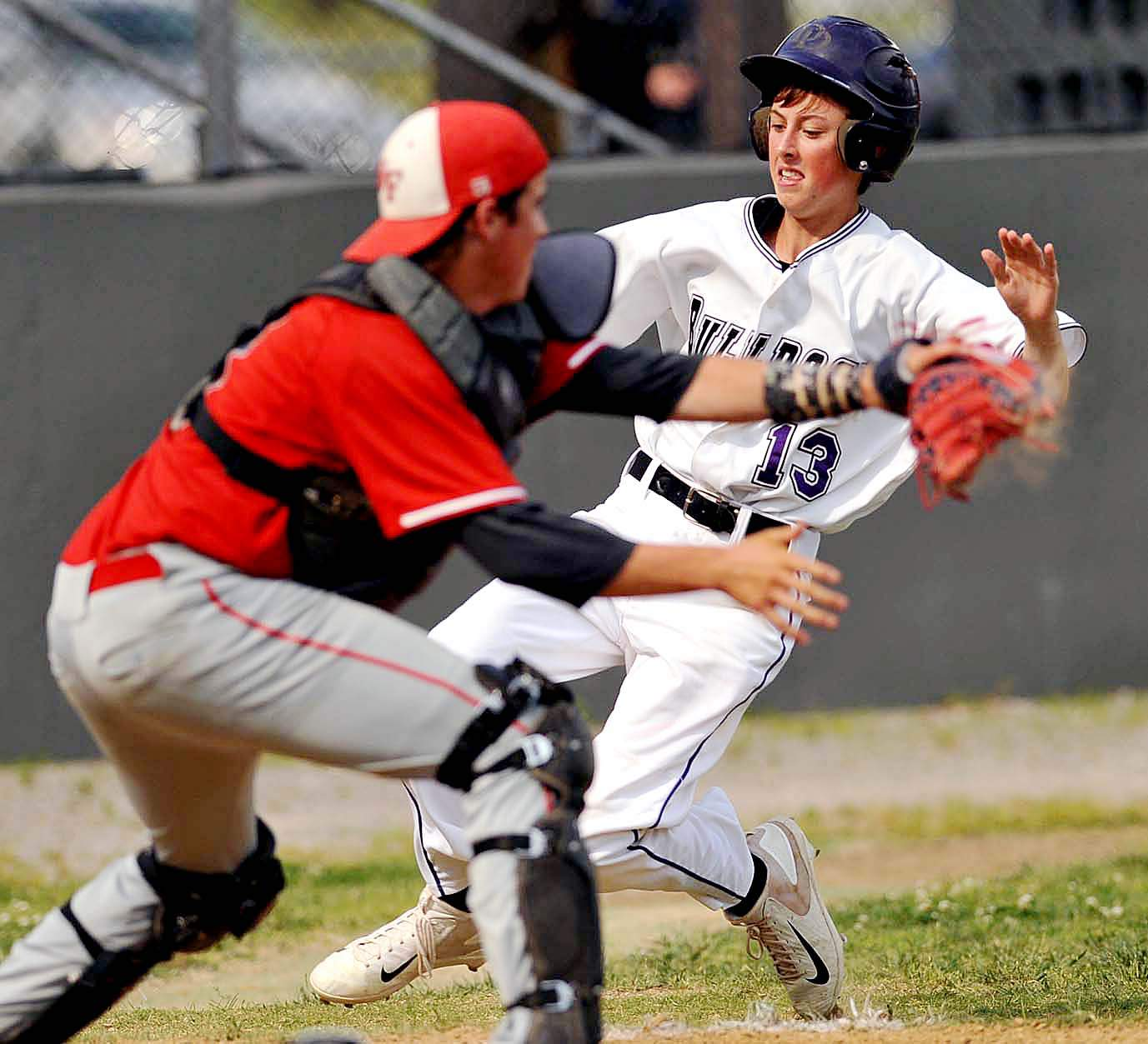 Harrisburg's Connor Phalin slides past the West Frankfort catcher for a score in the Bulldogs' 8-2 IHSA Class 2A Regional semifinal win over the Redbirds. Harrisburg will now face Benton Saturday in the title game.