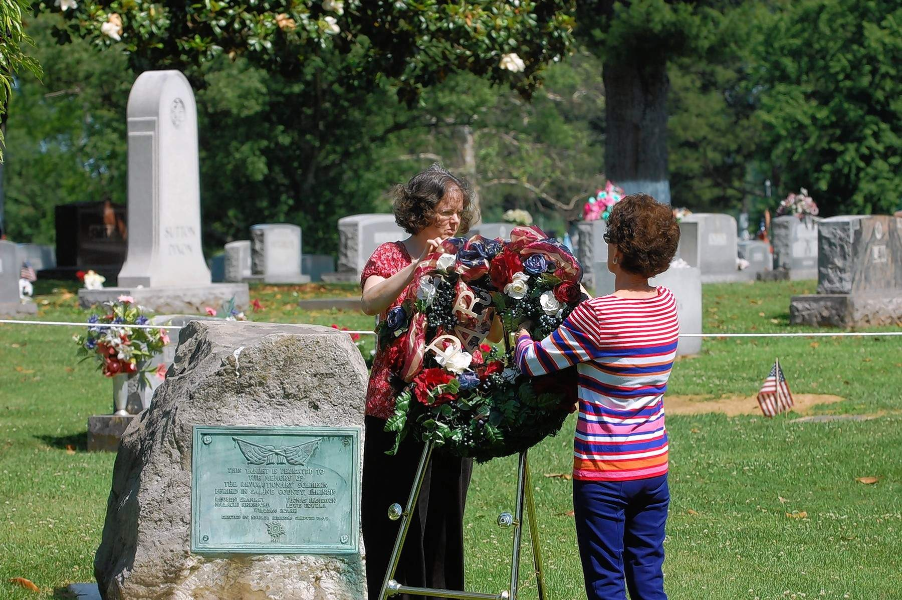 Daughters of the American Revolution members Sarah Drone, left, and Candy Duncan Evans place a wreath at Harrisburg's Memorial Day service Monday.