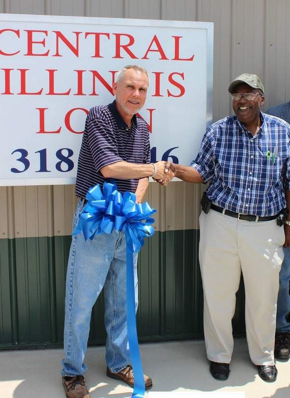 Rick Williams, branch manager of Central Illinois Loans, shakes hands with Pinckneyville Mayor Robert Spencer Friday at a ribbon cutting for the loan company's ninth branch office.