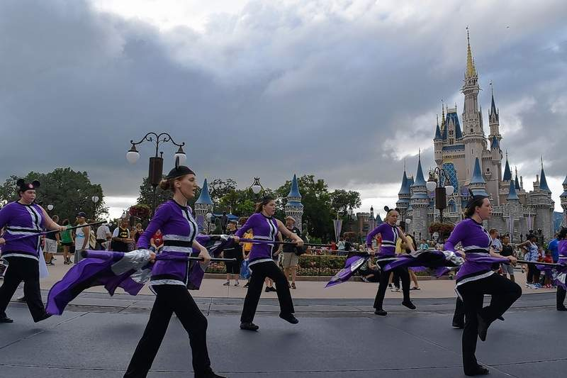Color guard members Halie West, front left, and Cierra Barnes, front right, perform in front of Cinderella Castle.