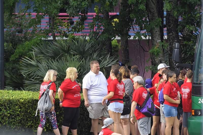 Band parent John Cummins, in white shirt, talks with other parent chaperones as the buses prepare to depart for Harrisburg on Thursday.