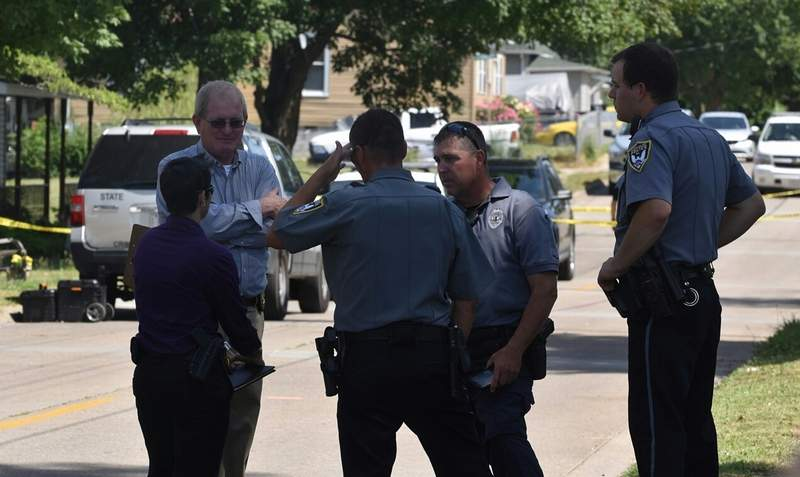 Police confer on the street in front of the Granger Street house where Aaron Gregory was shot.