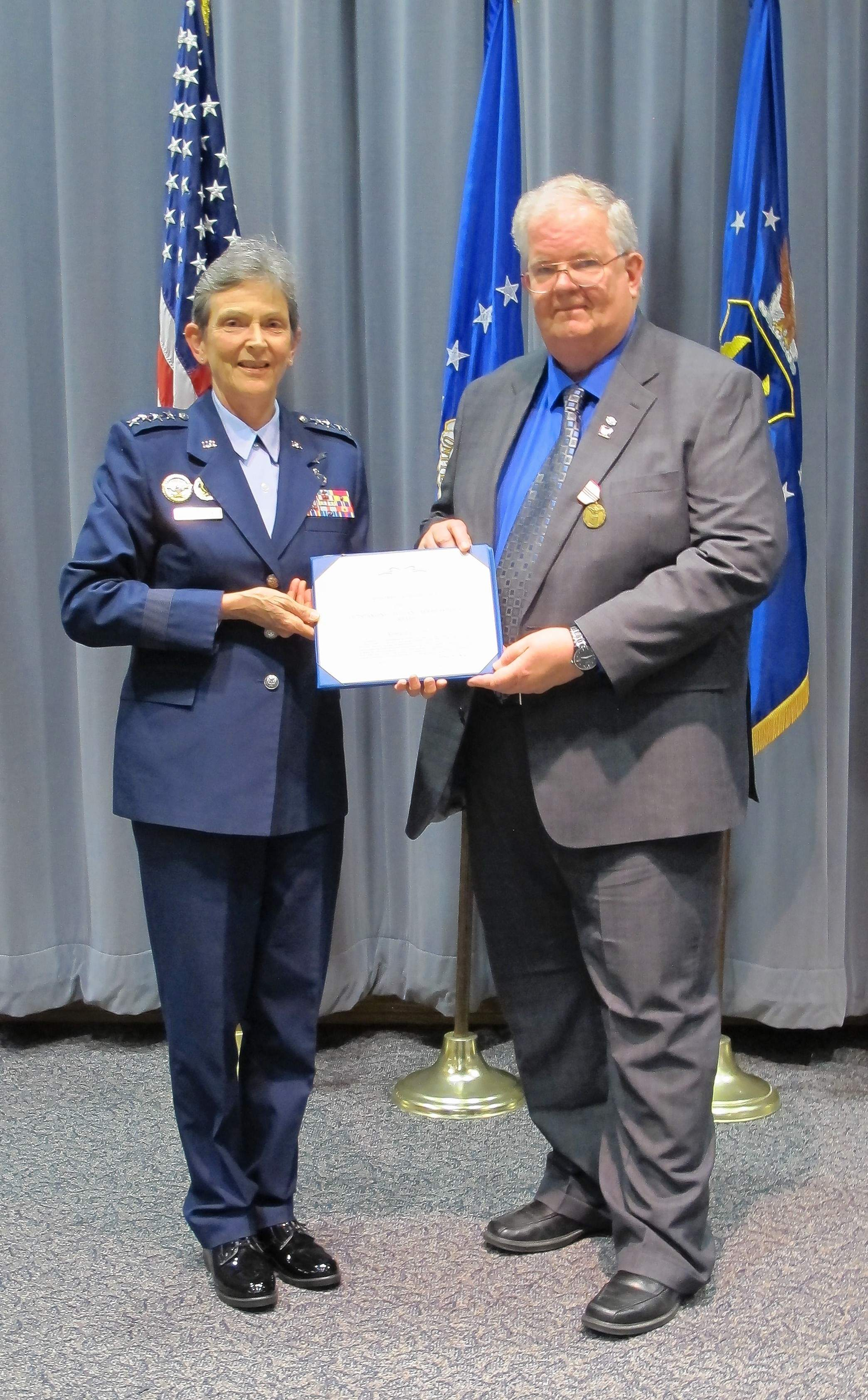Air Force Gen. Ellen Pawlikowski presents Eldorado native Ron Fry with the citation accompanying his Air Force Outstanding Civilian Career Service medal.