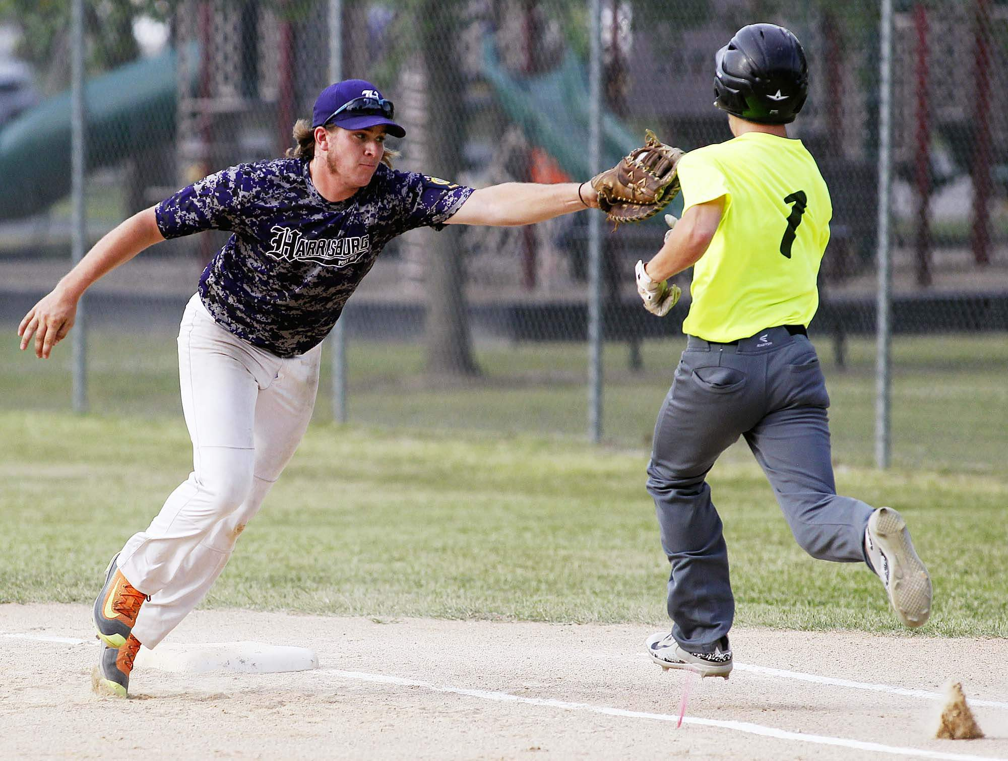 Harrisburg Post 167 first baseman Josh Turnage comes off the bag to make this tag on McLeansboro's Laban Cross in action Wednesday at Gibbs Field in District 21 action.