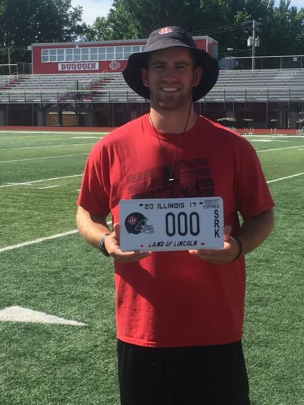 Indians football coach A.J. Hill poses with one of this year's license plates.