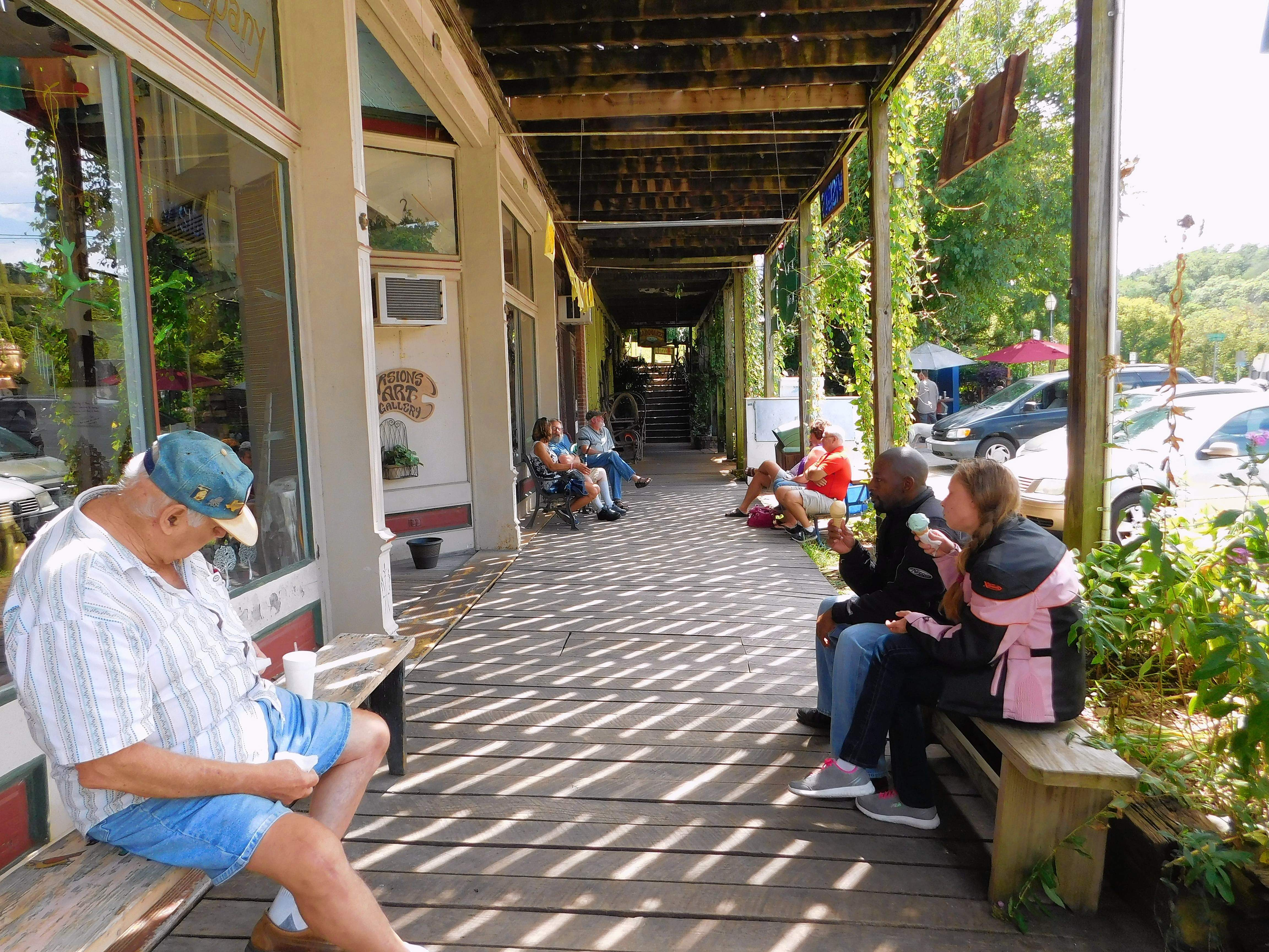 """Visitors enjoy a quiet moment and a little ice cream, on the Makanda boardwalk last weekend. Jason Richardson and Toni Cook, at right, live in Carbondale, and will not be in Makanda on Monday. """"I'll be watching it from the roof of our house,"""" said Richardson."""