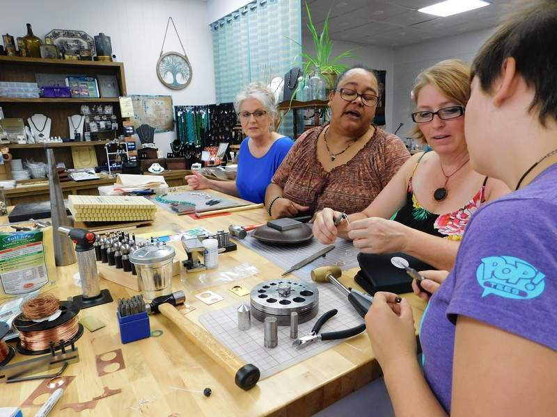 """Nicole Roundtree-Mileur, center, advises Heather Parr and Chloe Parr with their eclipse earrings at Saturday's jewelry making class. Sharon Mausey, behind, said she likes making wearable jewelry. """"This is my second class,"""" she said."""