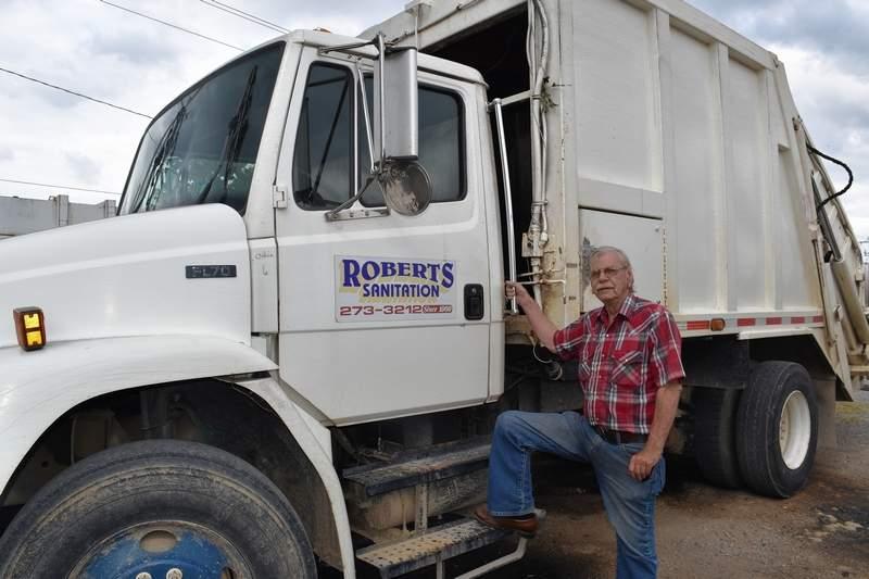 Kenny Roberts of Roberts Disposal in Eldorado, with one of his garbage trucks.