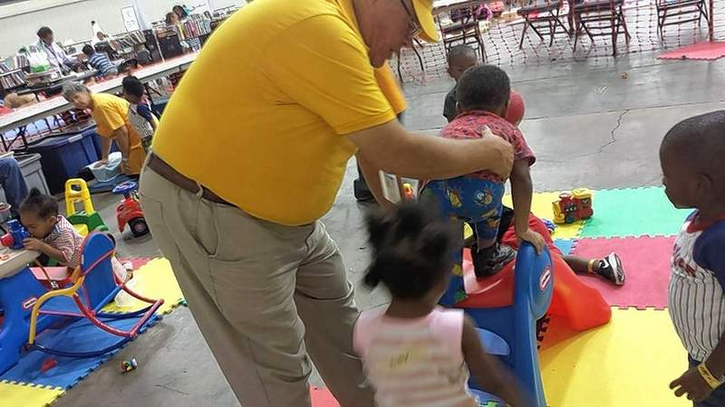 Former Johnston City Middle School band director Don Kragness plays with youngsters in his charge in a Dallas evacuation center.