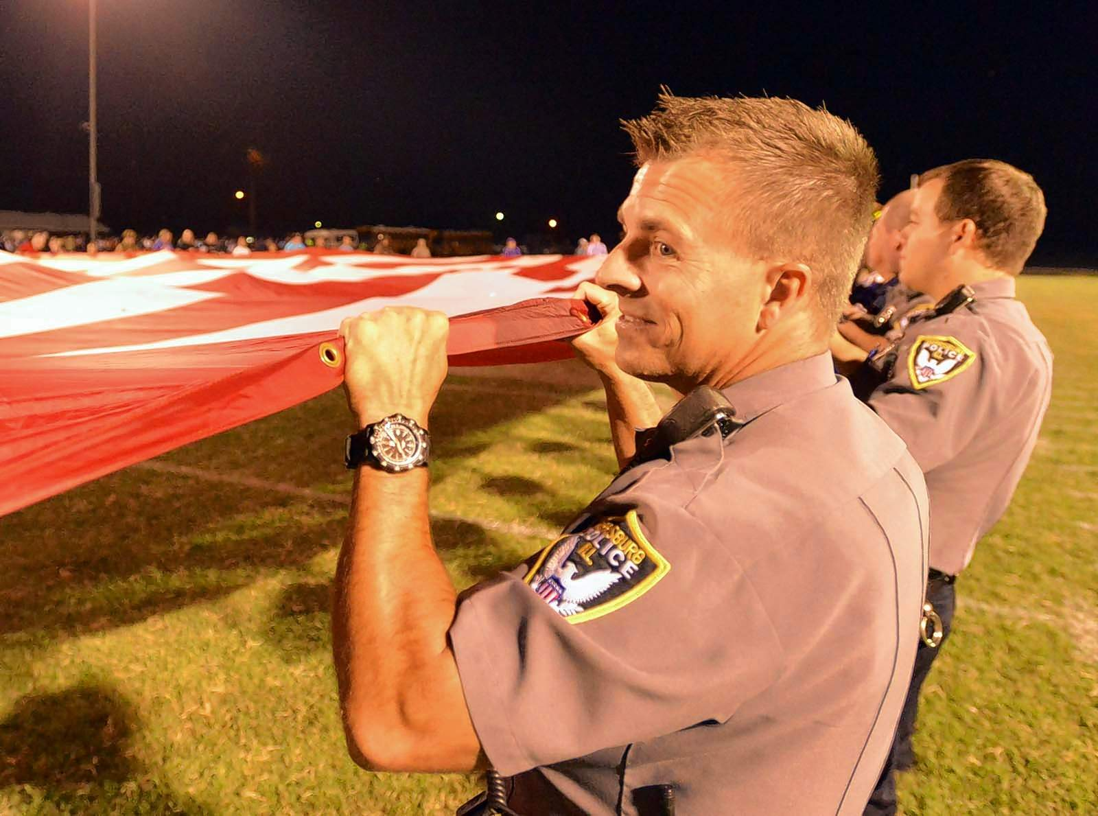 Harrisburg Police officer Brent Davis did his part in holding up the large American flag Friday during halftime festivities at the 9-11 remembrance ceremony at Taylor Field.