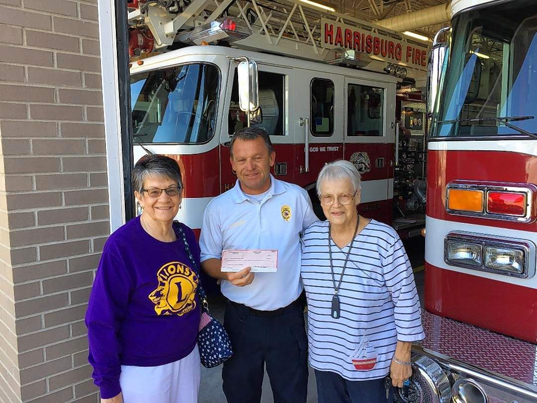 Harrisburg Town and Country Lions members Shirley Cain, left, and  Loretta Oxford brought a $500 donation check from their organization Wednesday for the Harrisburg Fire Department's supply drive to help hurricane victims. Harrisburg Fire Chief John Gunning accepts the donation.