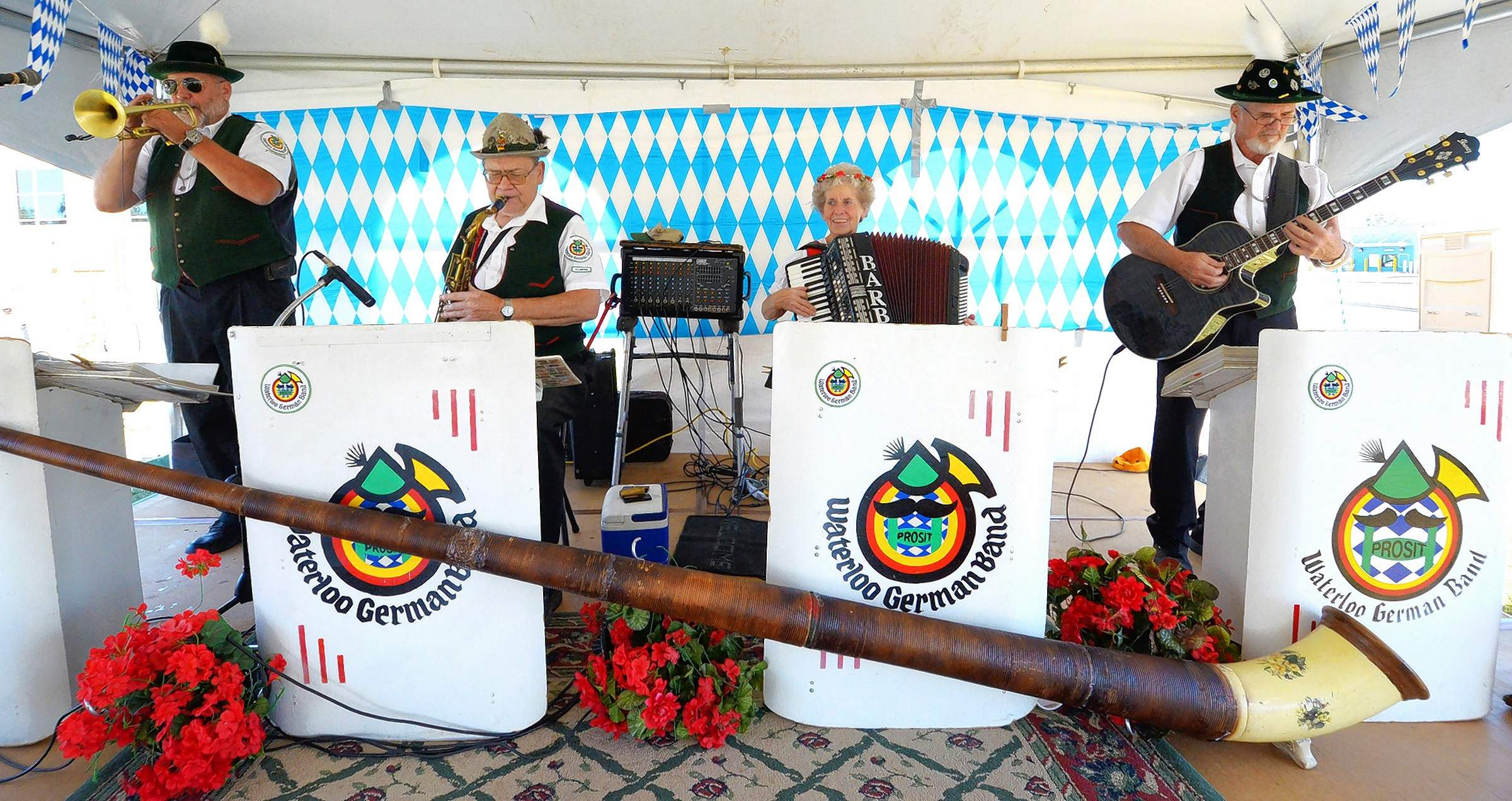 Above, members of the Waterloo German Band provided a musical backdrop for those who attended Saturday's Oktoberfest at Marion's Zion United Church of Christ. Left, Church member Gene Ruehmkorff was busy at the grill Saturday cooking applewurst sausages for the hundreds of hungry guests.
