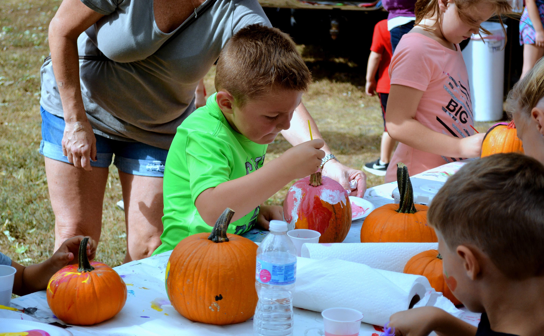Phoenix Mills, 5, paints a pumpkin in the kids corner.