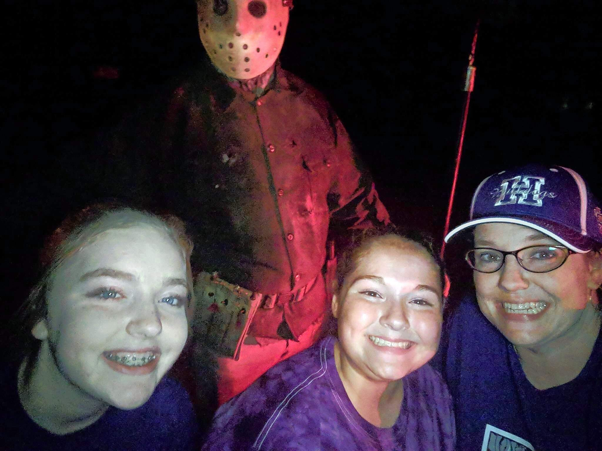 """From left, Gracie Behnke, Kirsten Eversmann and Elizabeth Eversmann of Harrisburg pose with """"Jason,"""" portrayed by actor C.J. Graham, at the Coleman Tri-County Services 25th haunted forest over the weekend."""