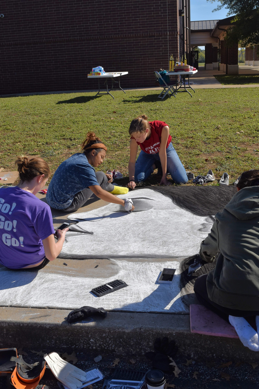 Harrisburg High School student Jasmine Teston, center, does some detail work on the team's sidewalk chalk art entry Friday along with Ashley Church, right, and Sierra Harrington.