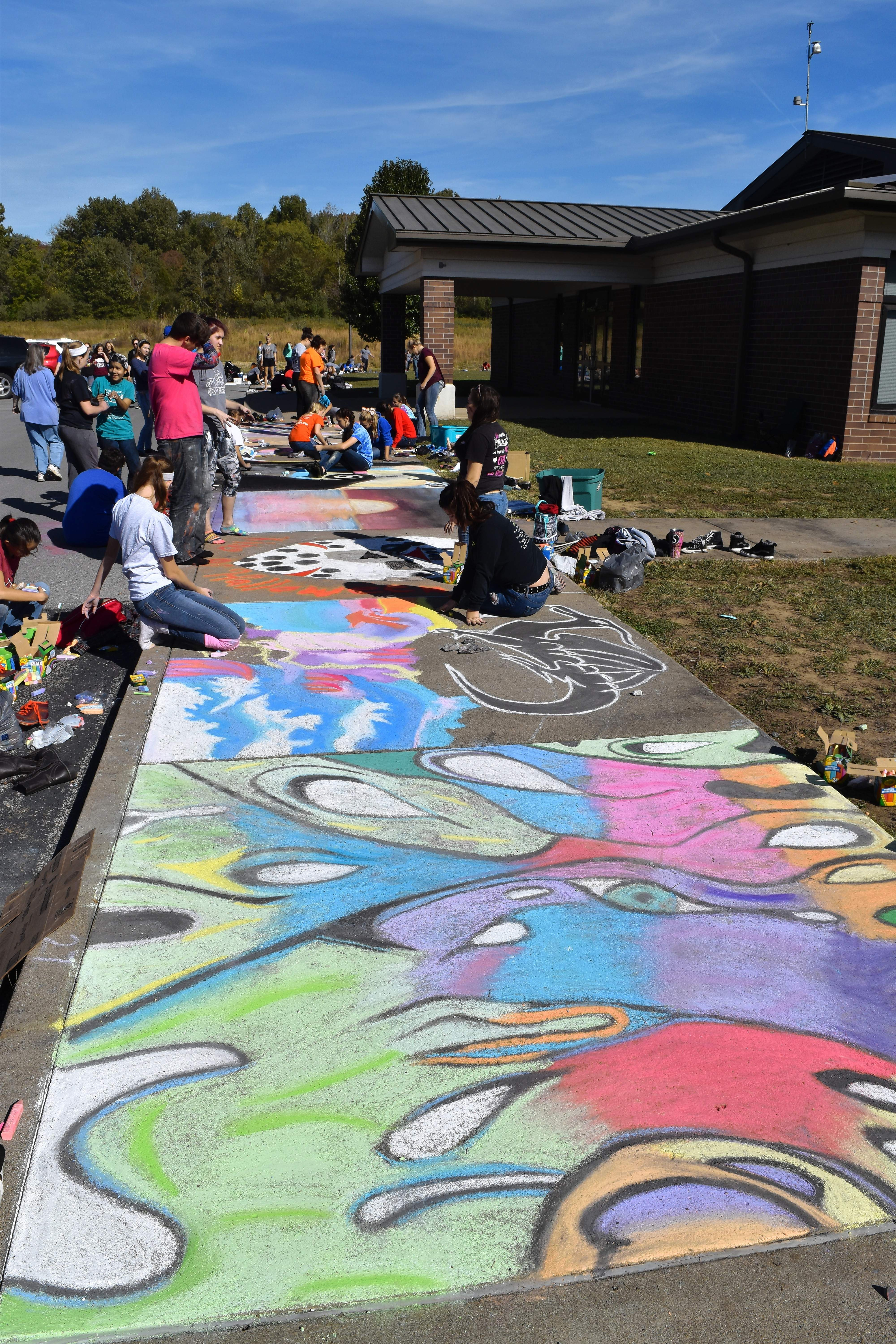 Harrisburg High School's sidewalk chalk art contest Friday featured 13 area schools. The chalk drawings surround the sidewalk on the west side of the school.