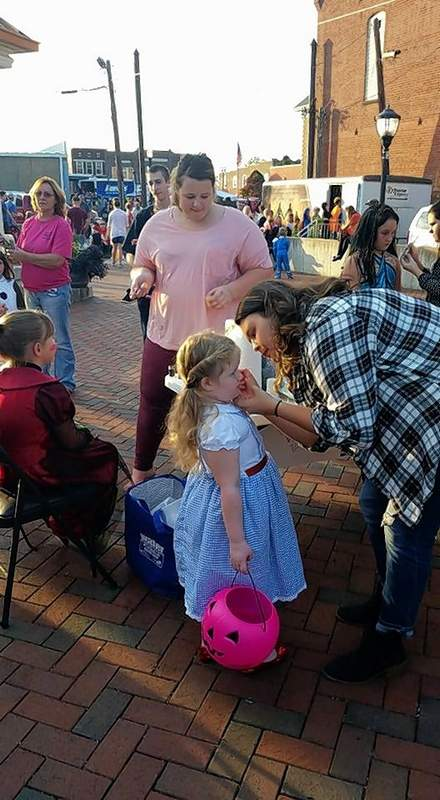 A representative from the Benton High School Student Chamber creates art on the face of a participant at last year's Benton Fall Fest.