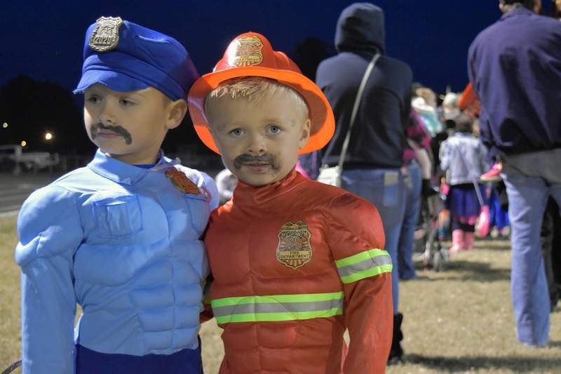 Twin brothers Kai, left, and Kree Morris wait in line at the Track or Treat event Tuesday night