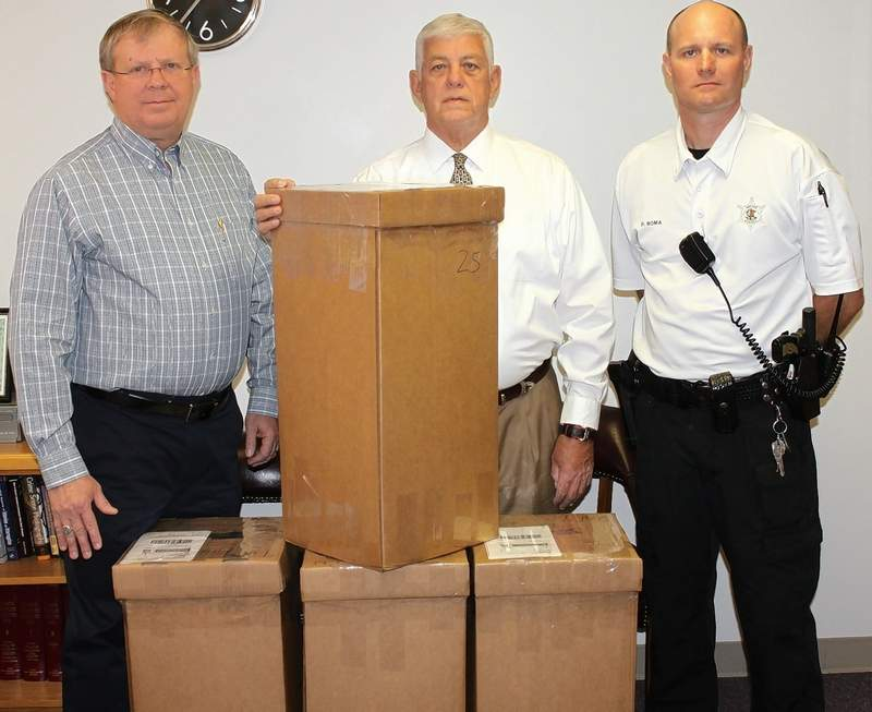 sheriff keith brown chief deputy ken clore and security officer pat boma with boxes containing