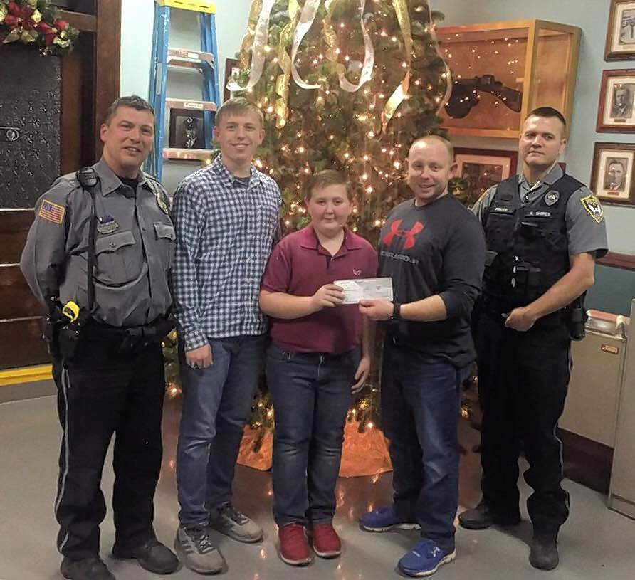 Lance and Max Maynor of Harrisburg recently presented a donation to Harrisburg's Shop With a Cop program. They were recognized for their contribution prior to the city's most recent council meeting. From left are Harrisburg officer Curt Hustedde, Lance Maynor, Max Maynor, and Harrisburg officers Nathan Moore and Kenny Shires. The brothers raised $250 for the program.