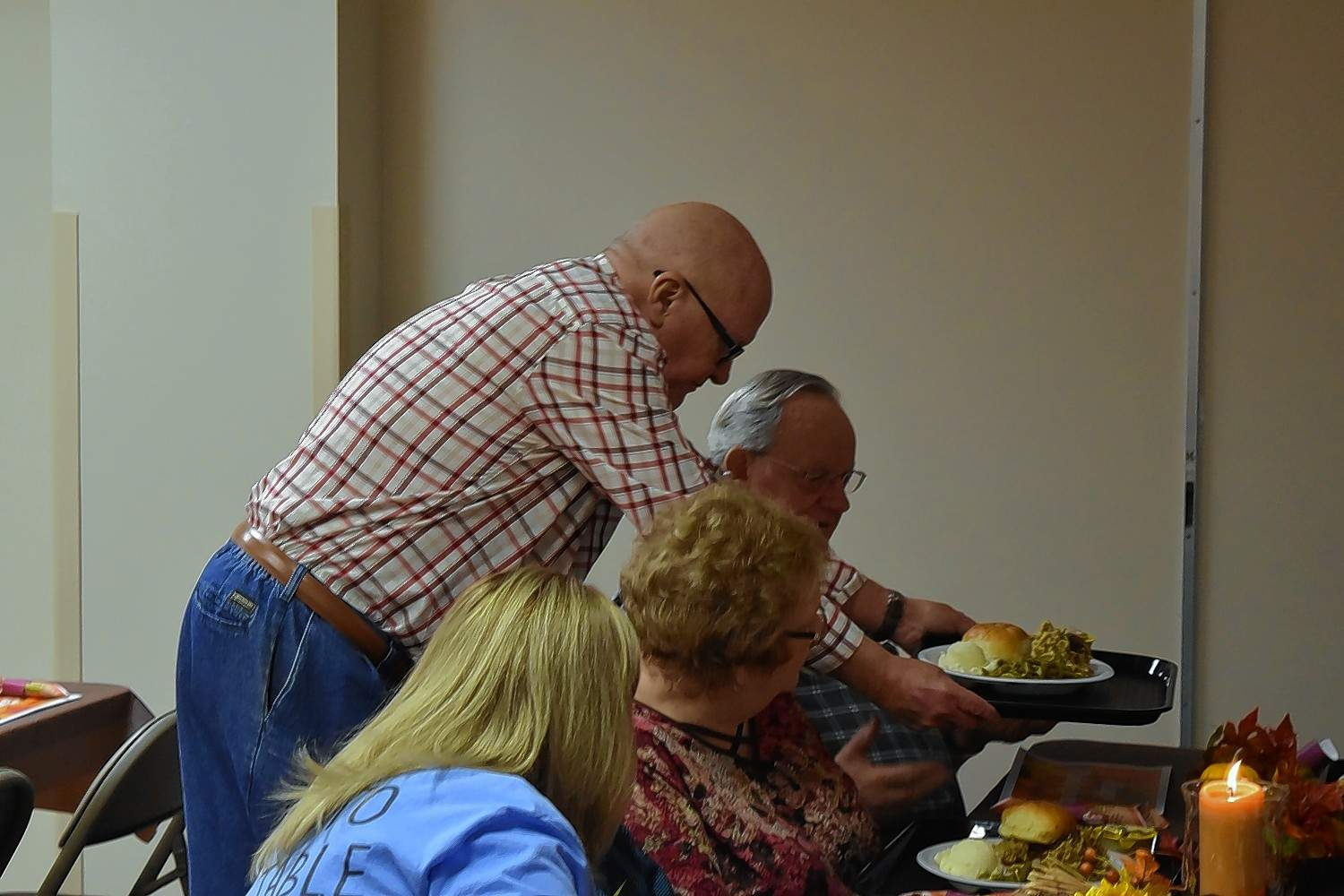 Volunteer Mickey Pankey delivers a plate of food to a guest at Harrisburg First Baptist Church's 'His Table' community dinner.