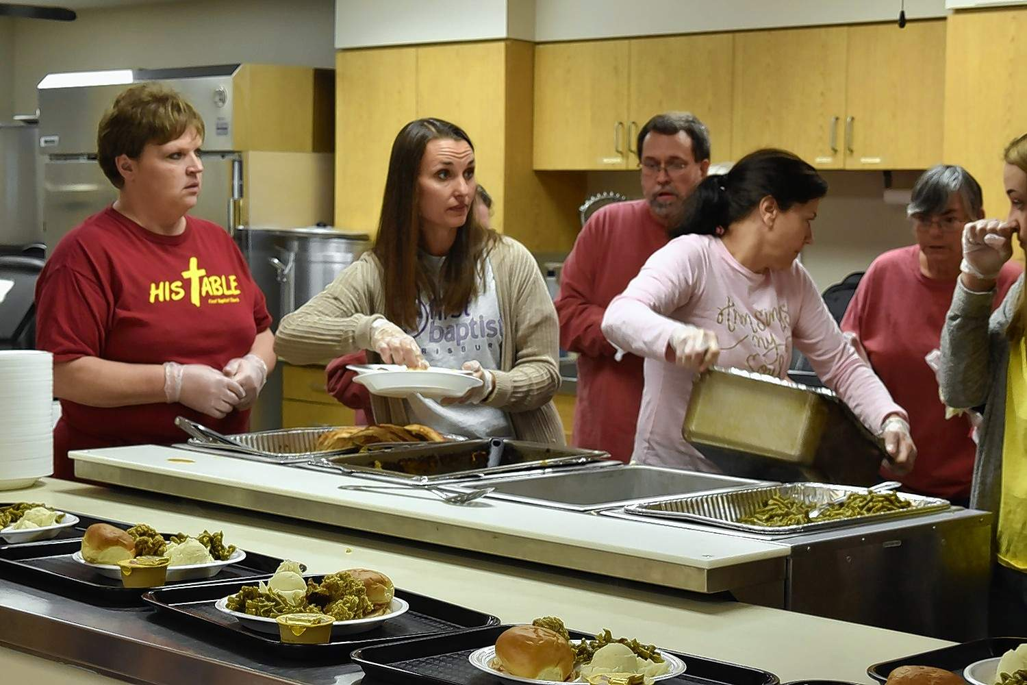 First Baptist Church kitchen volunteers Angie Henson, left, and Laura Winkleman prepare plates for guests Thursday afternoon. TURN TO PAGE 3 MORE PHOTOS.