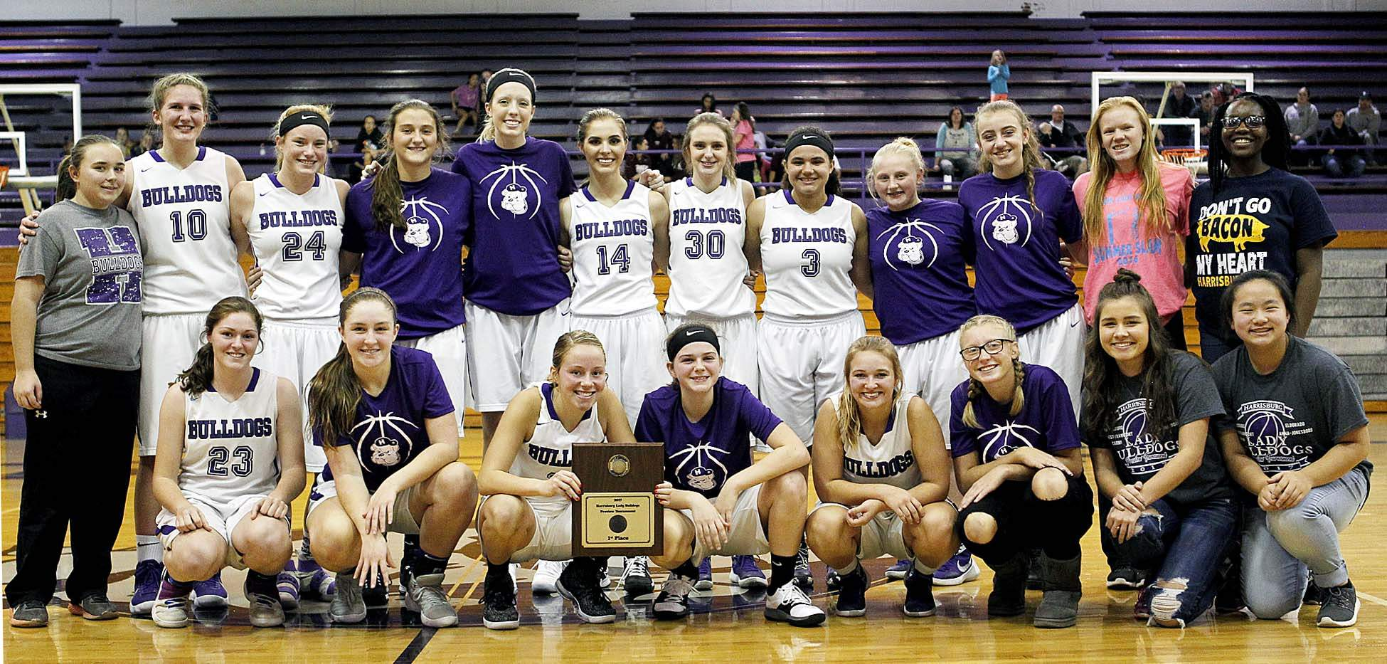 Members of the Harrisburg girls' basketball team pose with the championship plaque after the Bulldogs went 4-0 in their own invite. Harrisburg knocked off Eldorado 71-41 for their third straight title.