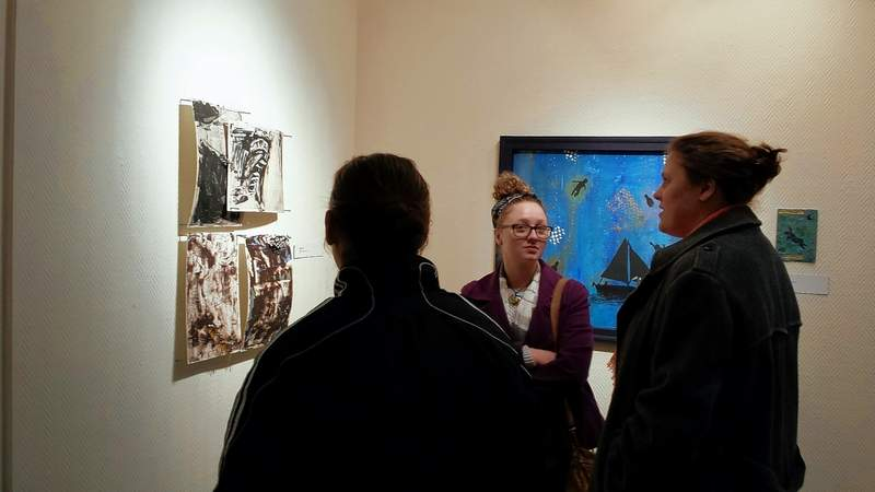 SIUC art students Anna Wonnell, center, and Camille Ticheur discuss Ticheur's work hanging in the SIC art gallery Thursday night.