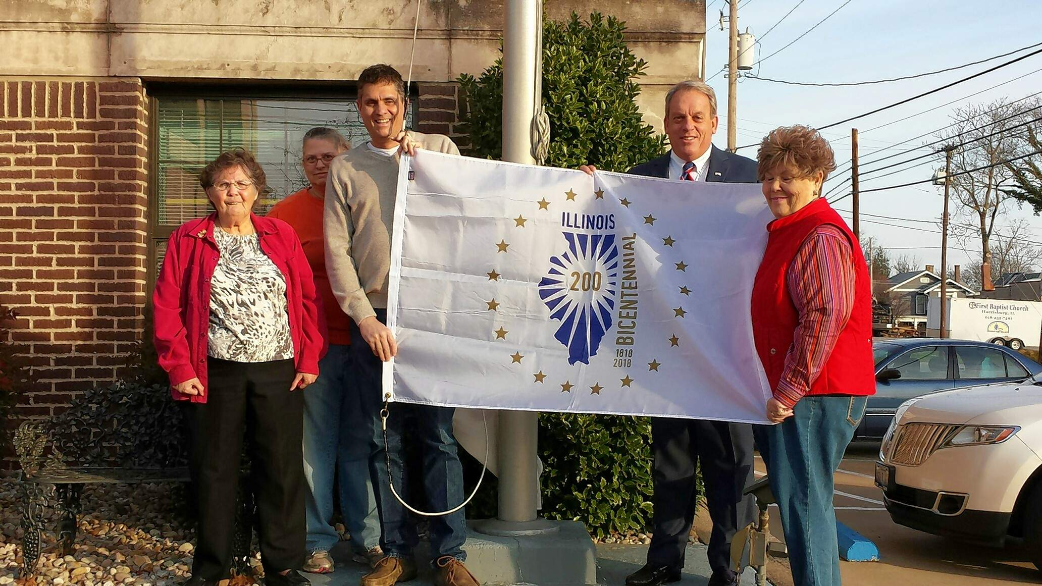 Harrisburg raised its Illinois Bicentennial flag Monday morning at city hall. From left are Delores Vick, Michael Hillegas DAR Bicentennial Committee, Harrisburg Mayor John McPeek, State Sen. Dale Fowler, R-Harrisburg, and Sharon Tanner, Michael Hillegas DAR Chapter Regent/Bicentennial Committee.